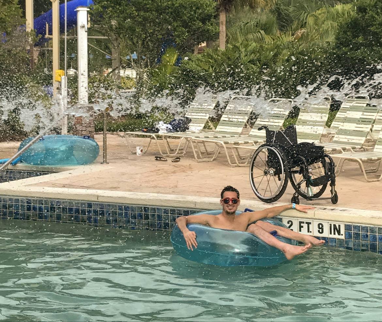 Danny floating in a tube in the pool at Orange Lake Resort