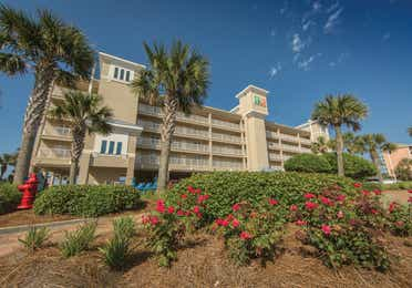 Property building with palm trees  and floral landscaping at Panama City Beach Resort