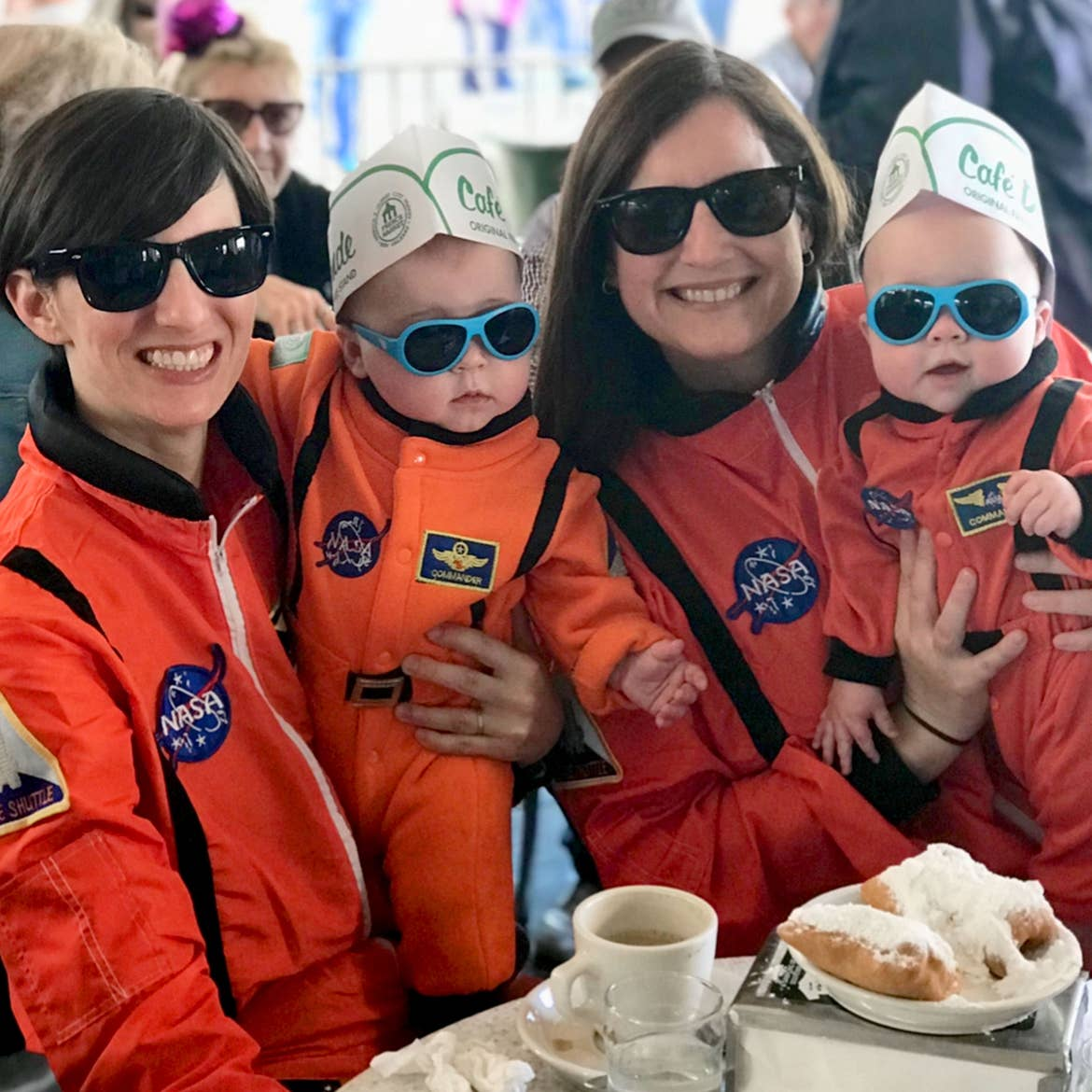 Featured Contributor, Catherine Karas, and her family enjoy beignets indoors dressed in orange astronaut suits.