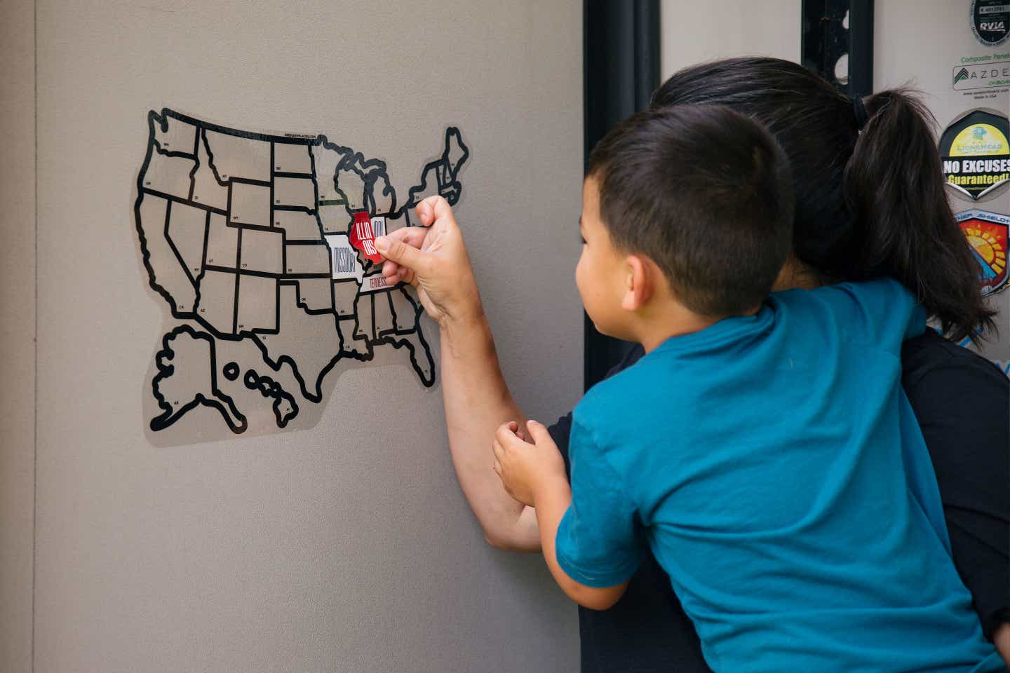 Angelica helps her son place a sticker for Illinois on their RV sticker map to indicate where they traveled.