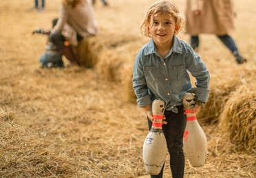 Child carrying bowling pins in hay.