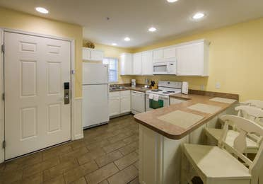 Kitchen with fridge, microwave, dishwasher, oven, and sink and kitchen bar in a one-bedroom Presidential villa at Hill Country Resort in Canyon Lake, Texas