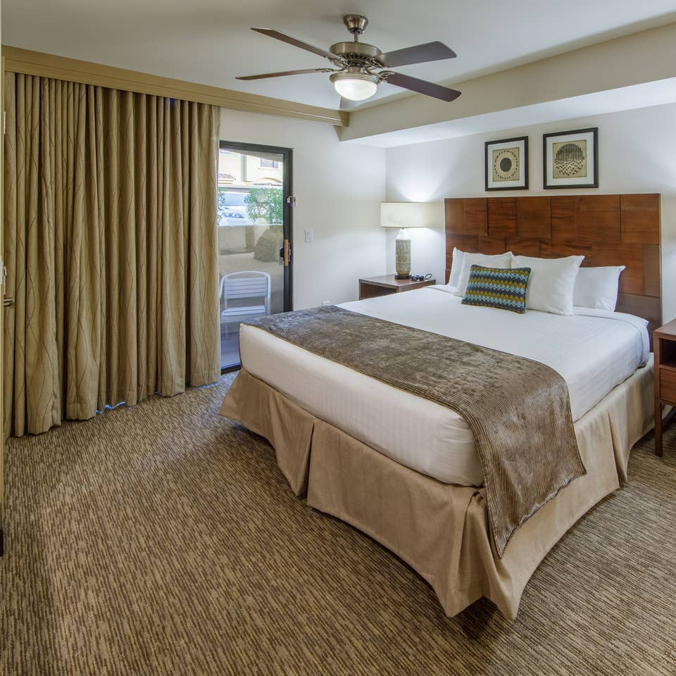 Master bedroom with access to balcony in a one-bedroom villa at Scottsdale Resort