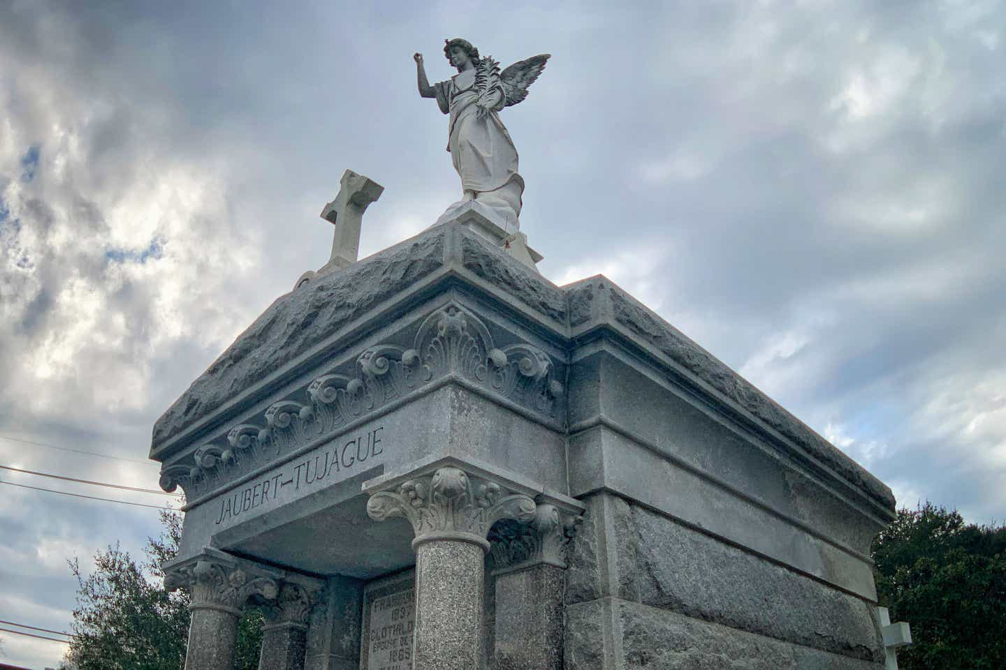 A grey stone mausoleum with a winged angel and cross on top in the St. Louis Cemetery No. 1.