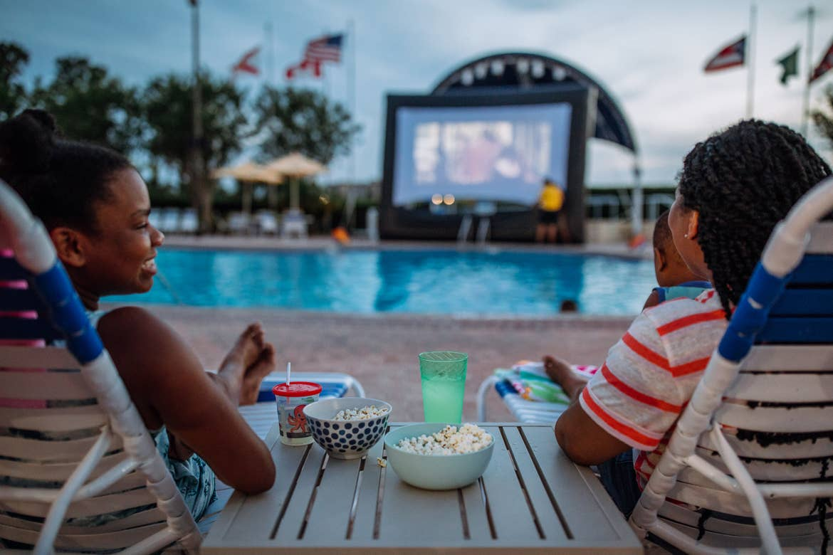 Krystin Godfrey (right) and daughter Sabria (left) enjoy watching a summer outdoor movie near the edge of the pool on a large inflatable screen.