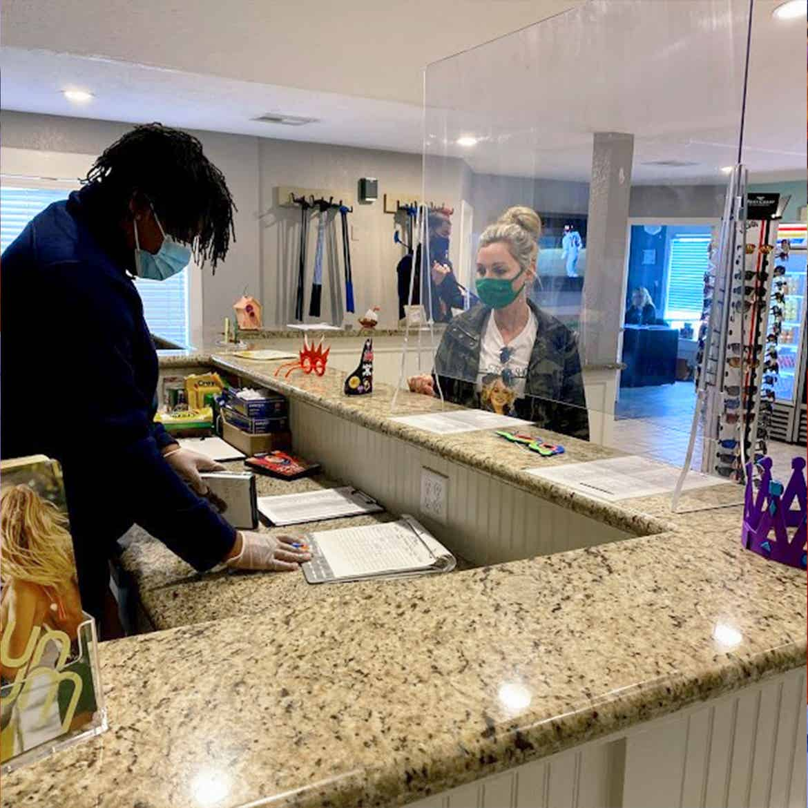 A Team Member assists Amanda with mini-golf equipment rentals while both wear a mask behind plexiglass at our Galveston Beach Resort.