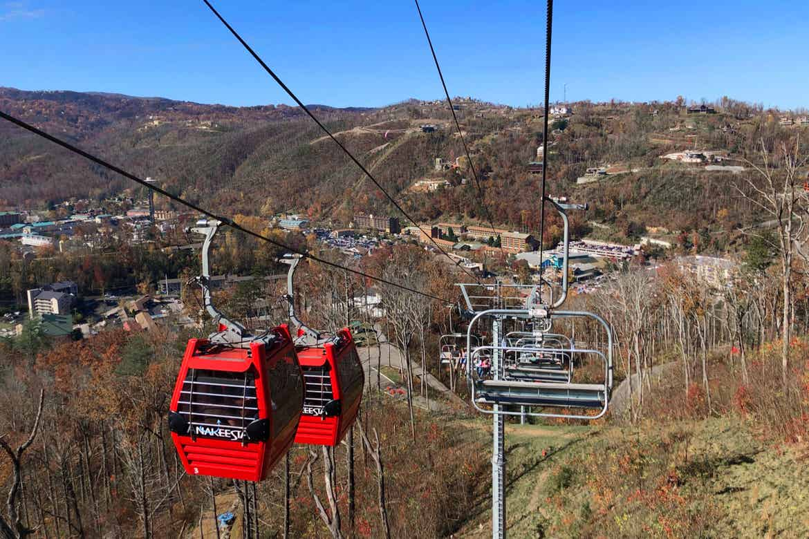 Two read gondolas (left) ascend while chair lifts (right) descend above the forested mountains of Tennesse.