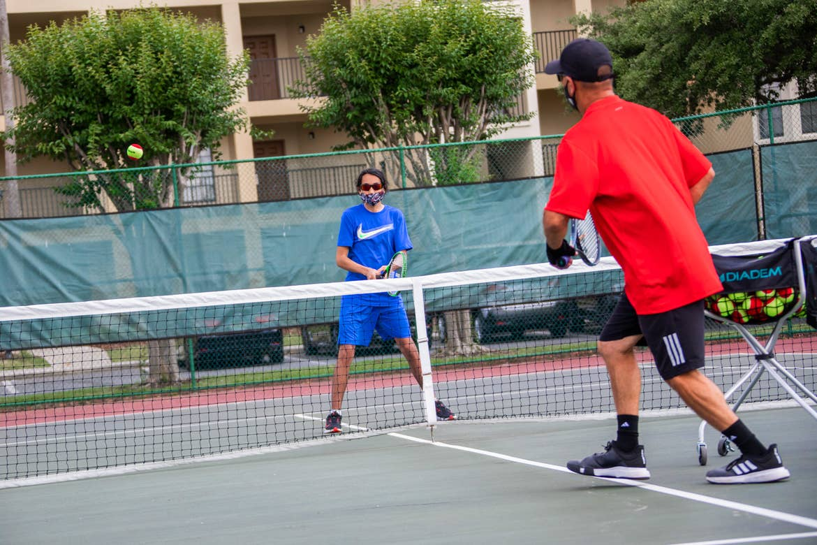 Special Olympic Athlete, Roan Luallen, plays tennis wearing a blue t-shirt and shorts with a safety mask and sunglasses with an instructor on the courts of our Orange Lake Resort located in Orlando, Florida.