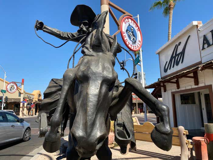 A cowboy statue in front of the Old Town Scottsdale sign with shops in the background.