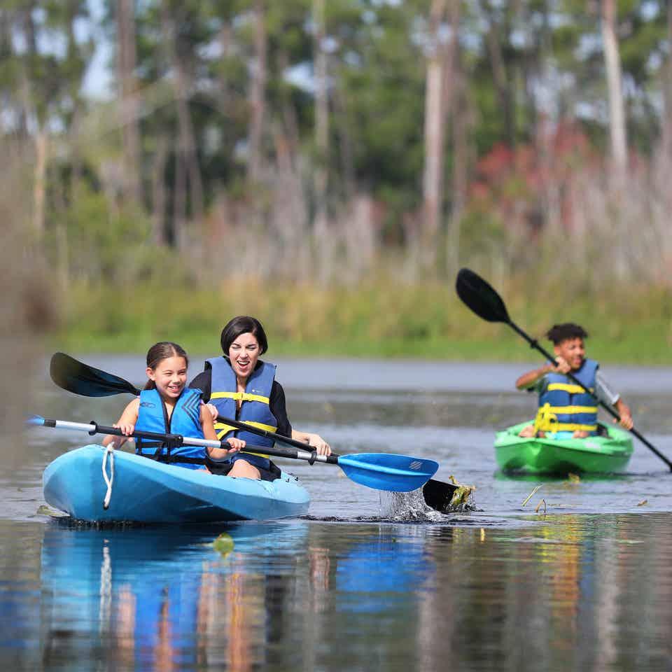Three visitors kayaking at Villages Resort in Flint, Texas.
