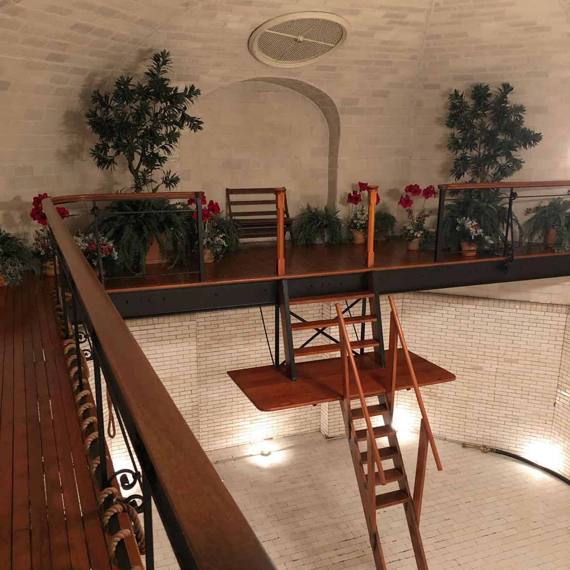 The empty indoor pool of the Biltmore Estate in the evening with an elaborate wooden ladder for swimmers surrounded by lush greenery.