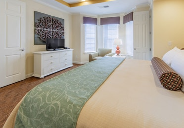 Bedroom with seating area by three windows and flat screen TV in a presidential villa at Fox River Resort in Sheridan, Illinois