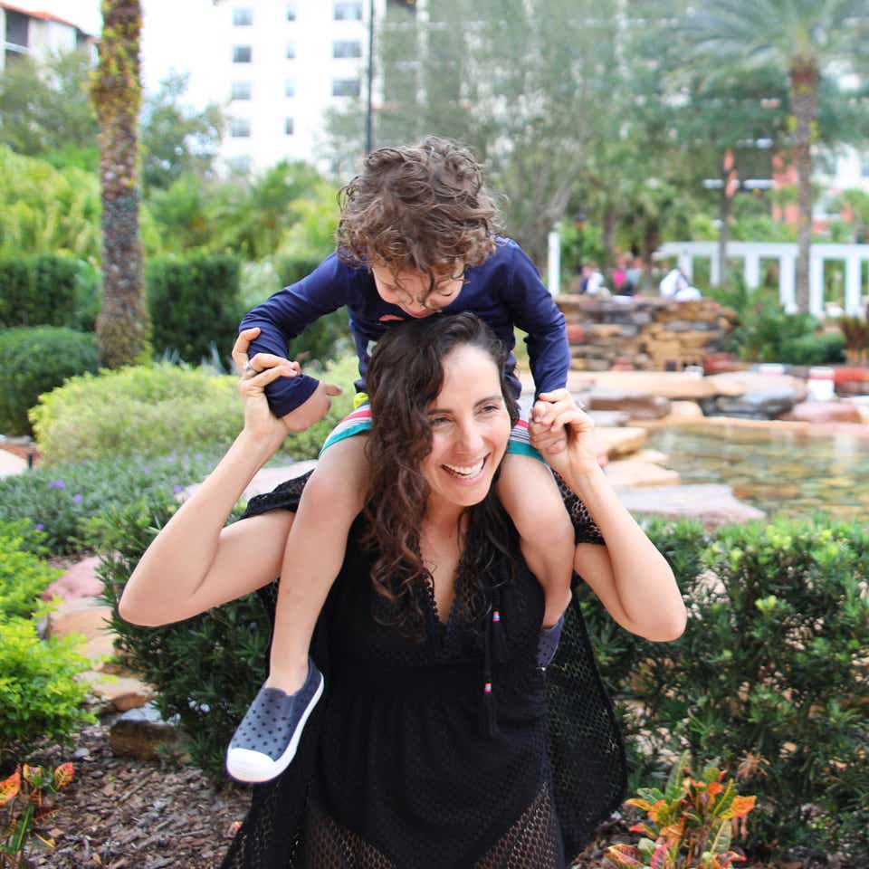 Woman laughing and carrying a child on her shoulders.