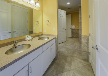 Full bathroom with double sinks and mirror in a presidential villa at Fox River Resort in Sheridan, Illinois