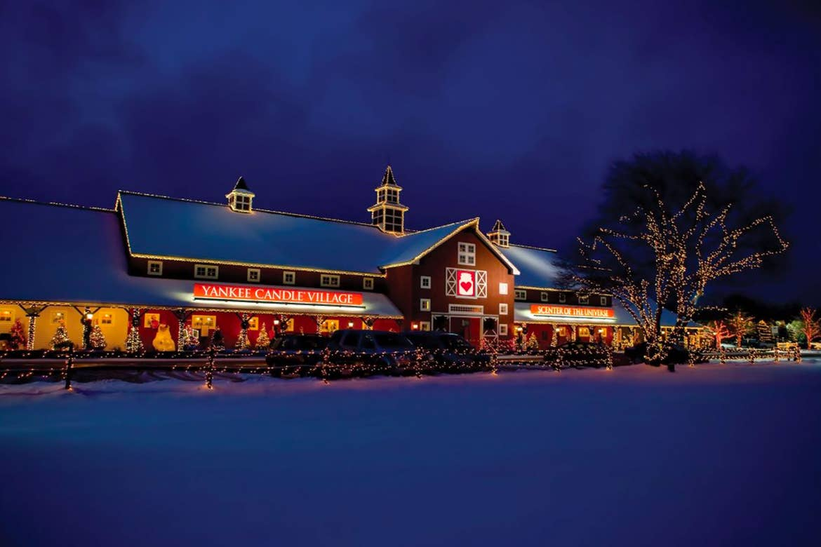 The exterior of the Yankee Candle Village storefront can be seen covered in white snow at night.