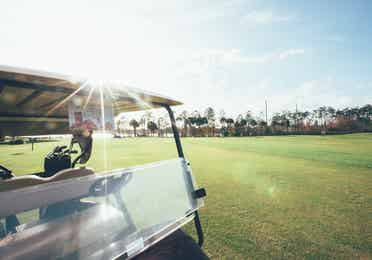 Golf cart driving on golf course in West Village at Orange Lake Resort near Orlando, Florida