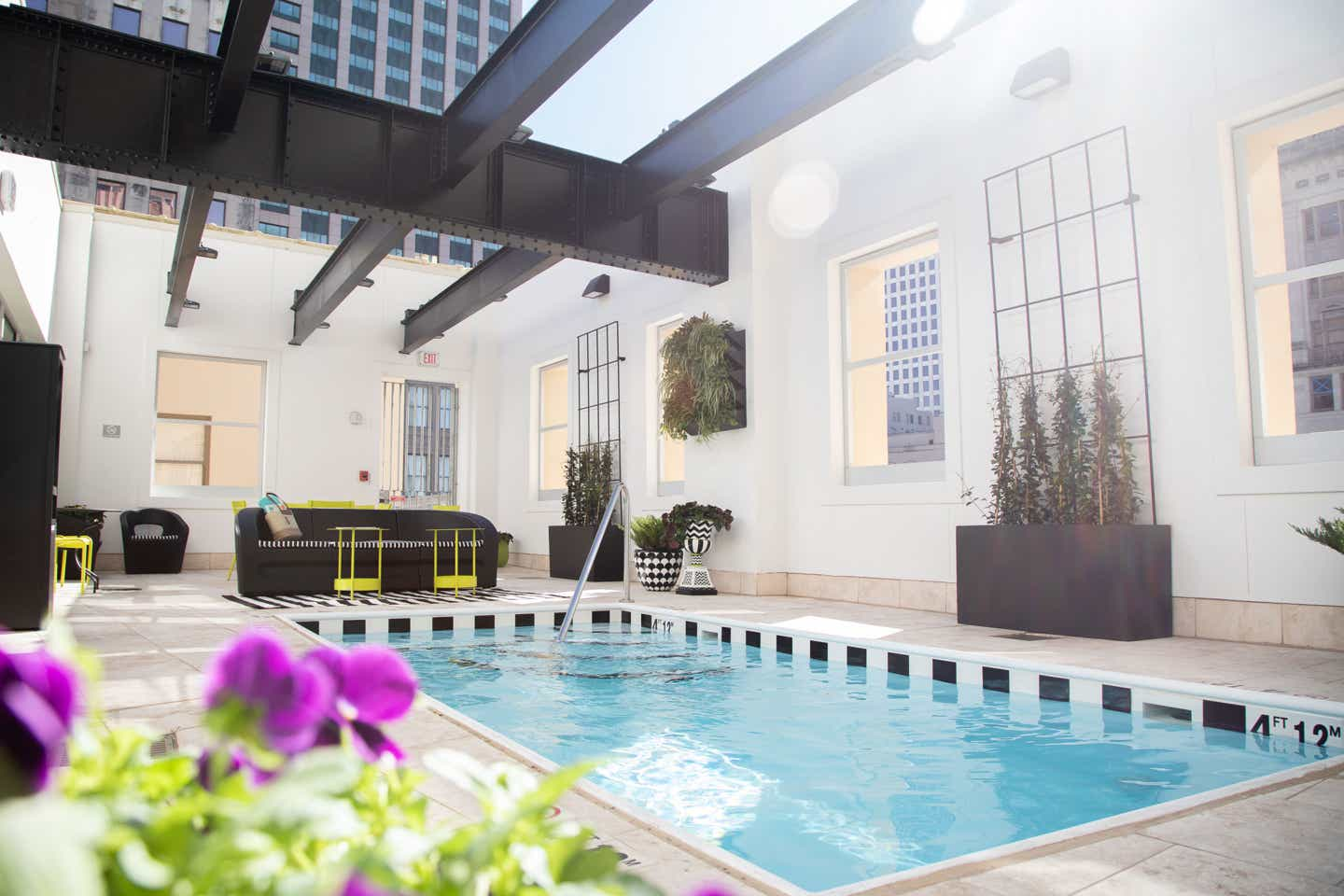 An exposed ceiling, rooftop dipping pool with black and lime green furnishings located in our resort in New Orleans, Louisiana.