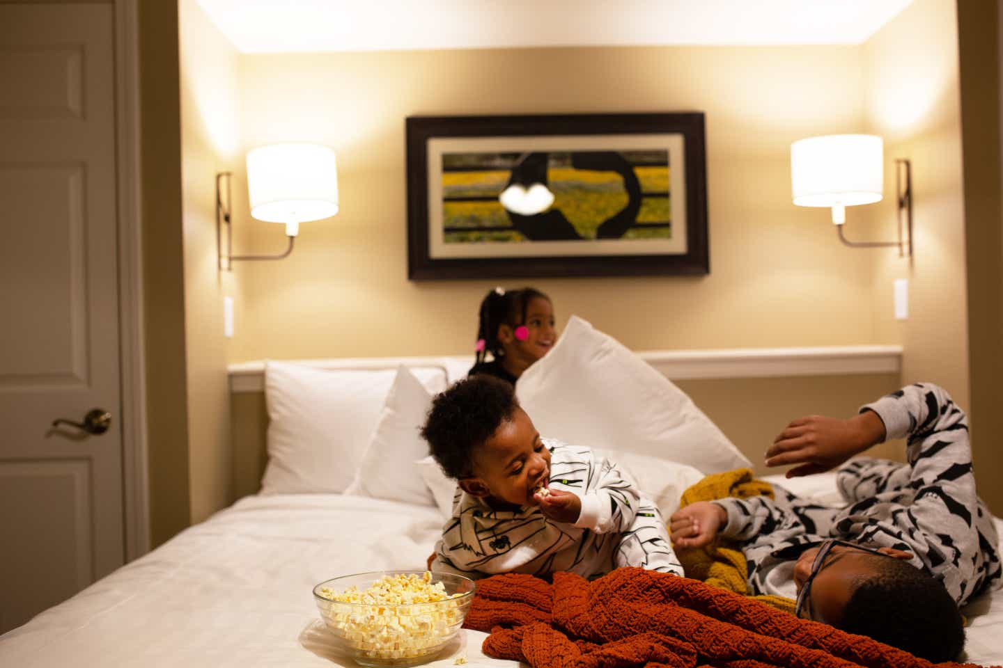 Tina's children laughing on the bed with a bowl of popcorn in their villa at Villages Resort.