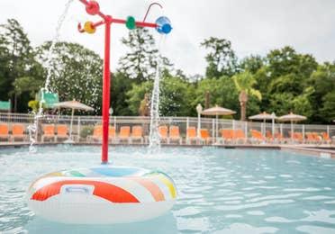 Tube floating in outdoor pool near splash buckets at Villages Resort in Flint, Texas.
