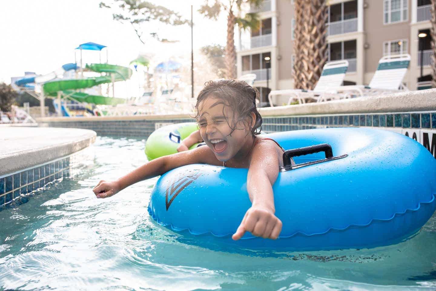 Brenda's daughter, Victoria, floats along the lazy river in a blue innertube.
