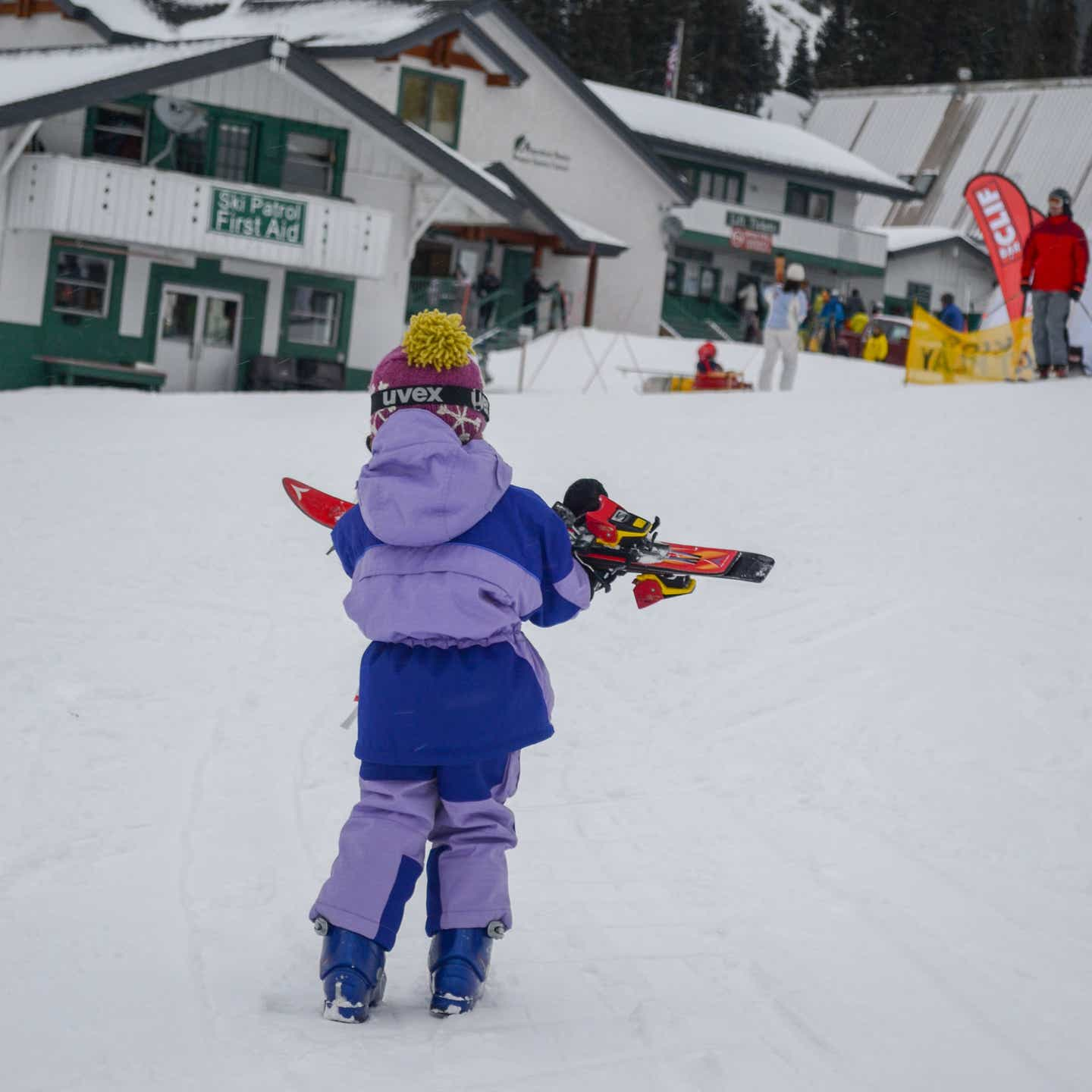 Jessica's daughter carries her skis to the slopes.