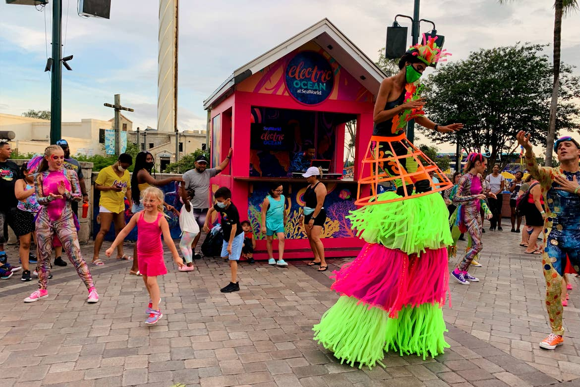 A group of performers dance in various costumes and on decorated stilts with visitors at Electric Ocean in SeaWorld Orlando.