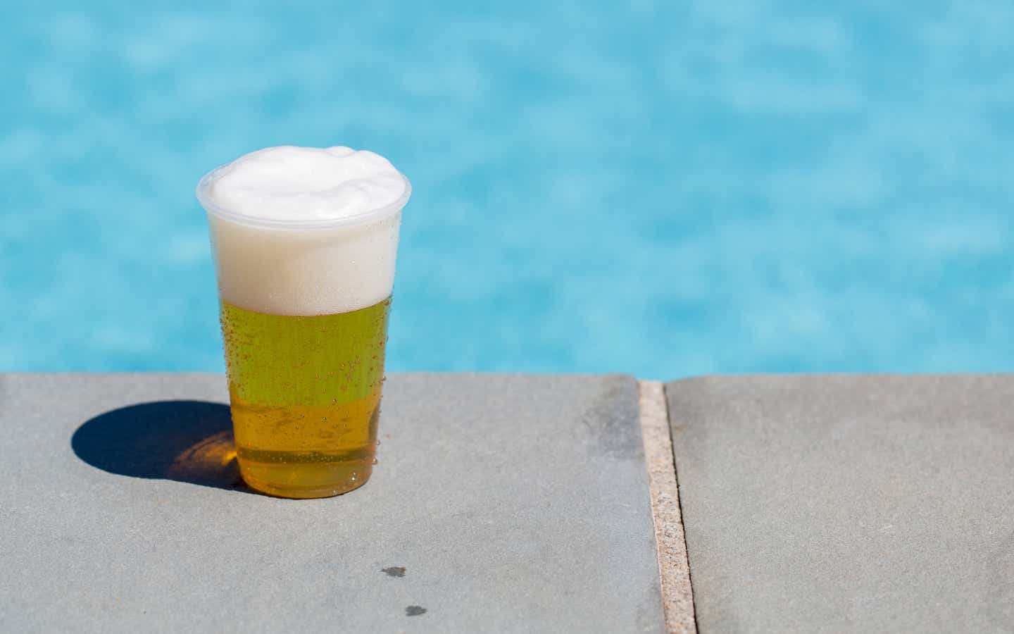 Glass of beer by an outdoor pool.