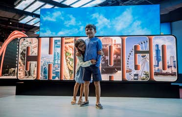 A young girl (left) embraces a young boy (right) in front of a sign that reads, 'Chicago.'