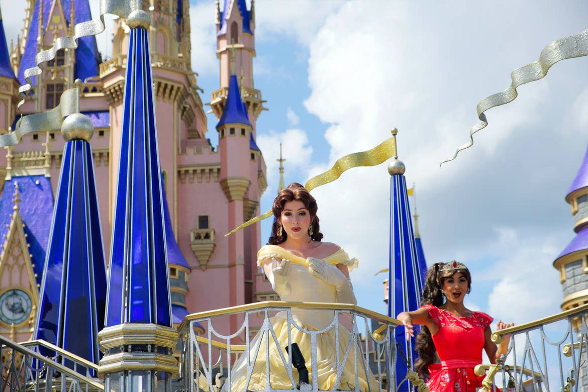 In front of Cinderella's Castle in Magic Kingdom, a parade float with Elena of Avalor (right) wearing her red ballgown and gold crown and Belle (front) wearing her yellow gown wave and blow kisses into the crowds during a character Cavalcade.