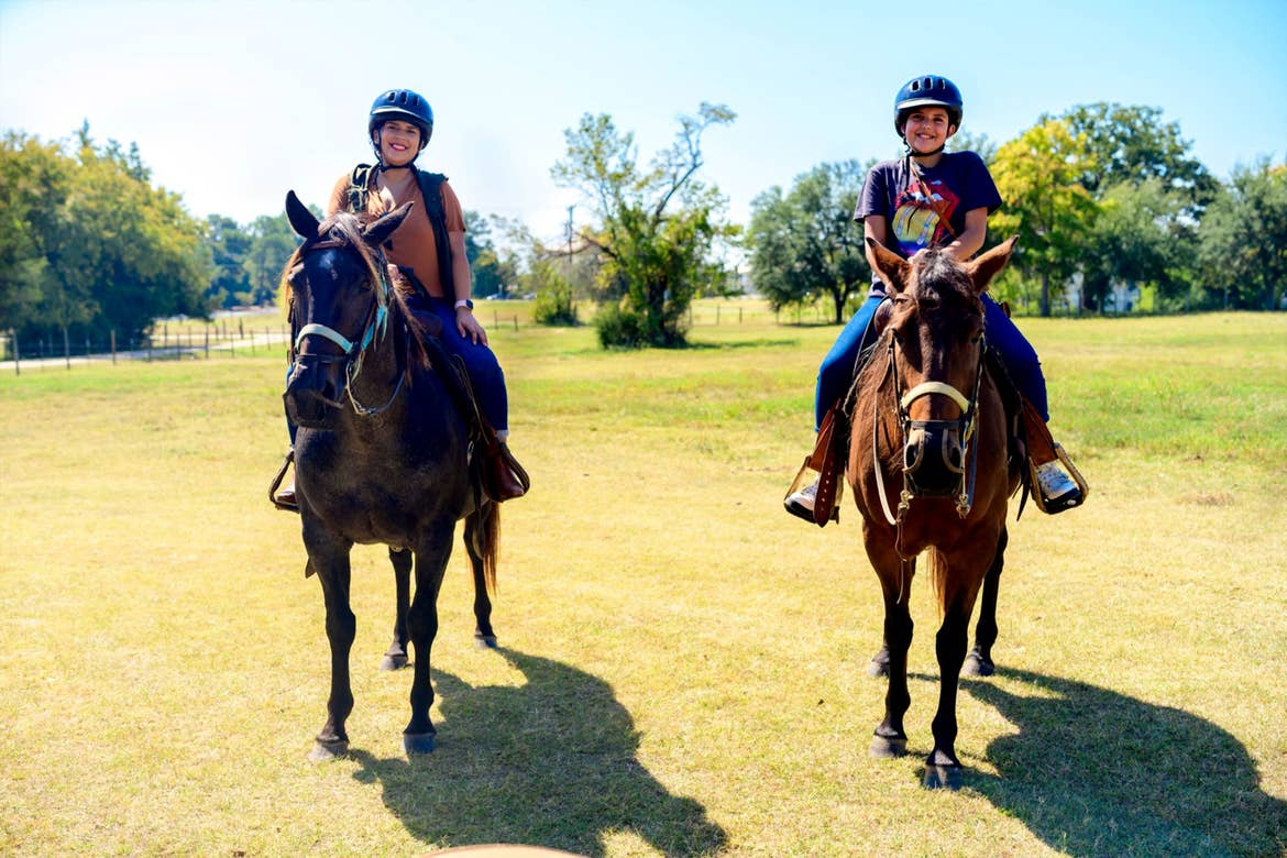 A woman (left) and tween girl (right) ride horseback in an open field.