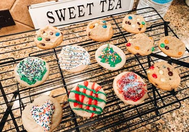 A baking rack containing sugar cookies with various icing decor.