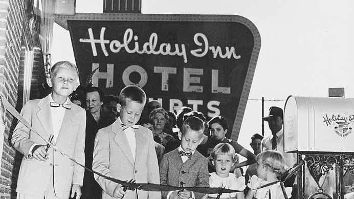 Kemmons Wilson cutting a ribbon at the first Holiday Inn with his family