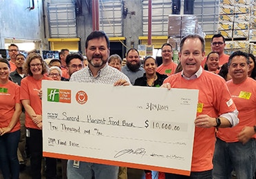 Tom Nelson, CEO of Holiday Inn Club Vacations Incorporated, presenting a large check to Second Harvest with a group of HCV employees behind him