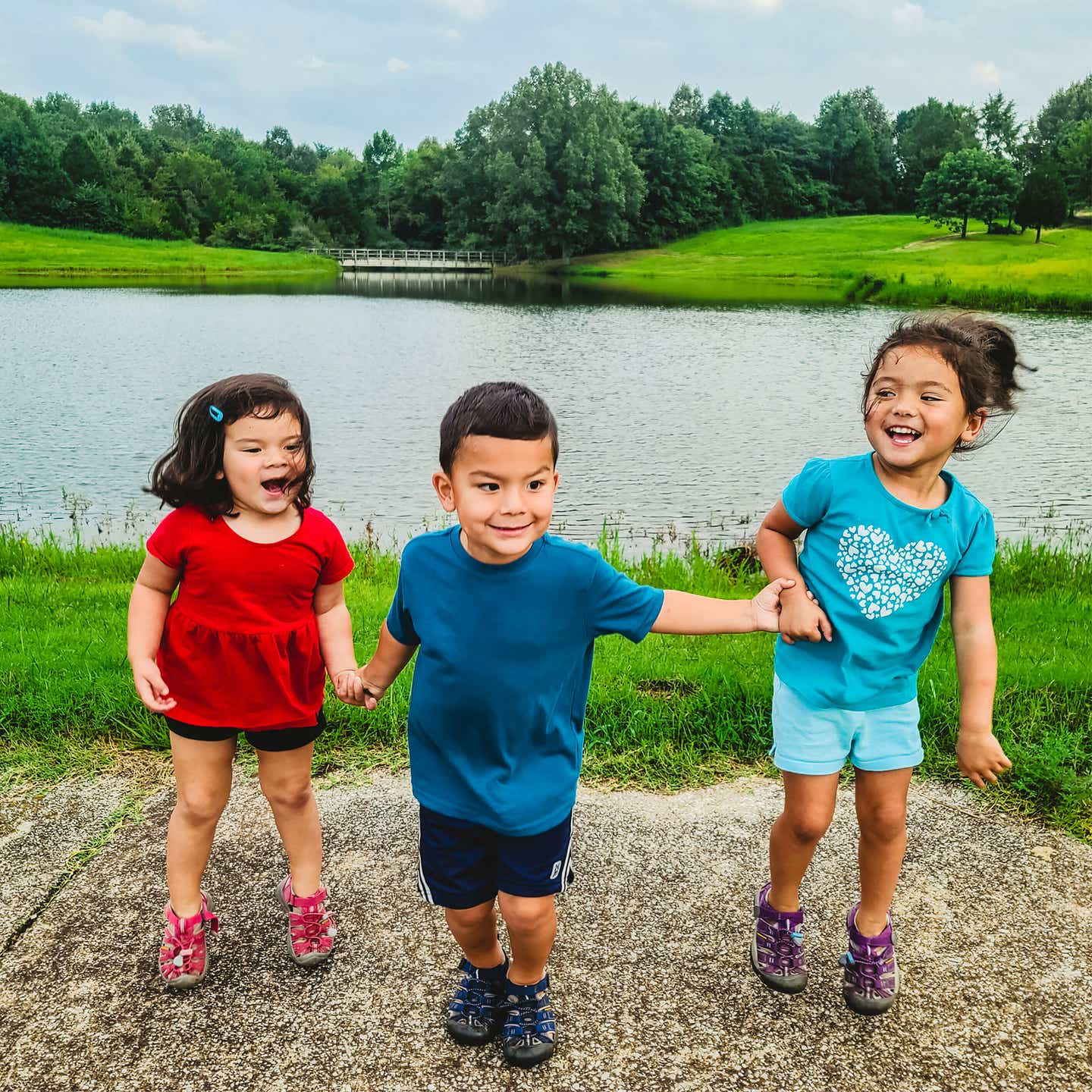 Angelica's three children smile happily in front of a pond in their RV park.