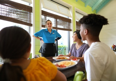 Family speaking to waitress in restaurant at Orange Lake Resort near Orlando, Florida