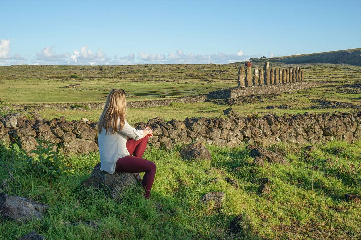 Featured Contributor, Ashlyn George, sits looking at the stone formations of Easter Island.