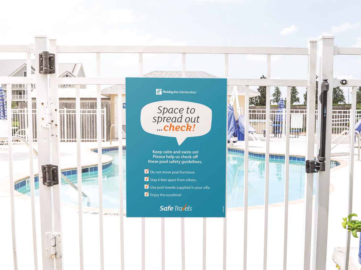 Safe Travels sign on the gate at a pool at a resort.