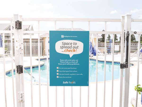 Safe Travels sign on the gate at a pool at a resort