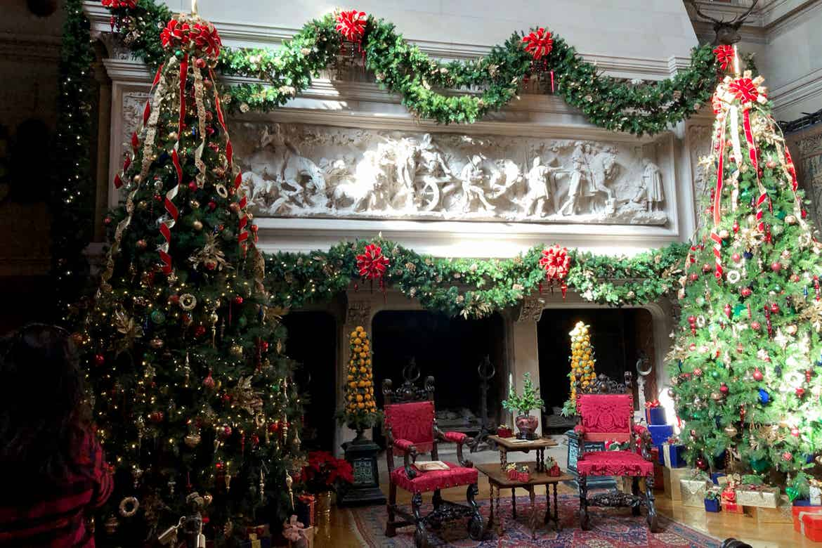The interior of the Biltmore Estate with an elaborate fireplace mantel decorated with lush Christmas garlands and surrounded by red seating and Christmas trees.