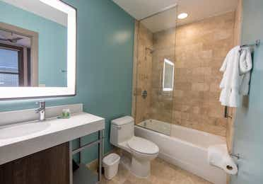 Bathroom in a one bedroom villa with shower/tub combo, toilet and sink with lighted mirror at New Orleans Resort in Louisiana.