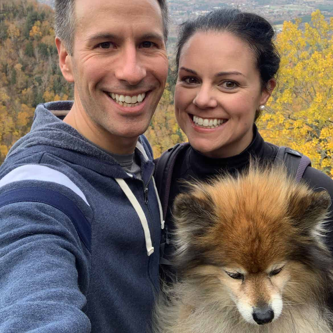 Authors, Lauren Layne and Anthony LeDonne, stand in front of fall foliage with Bailey the Pomeranian.