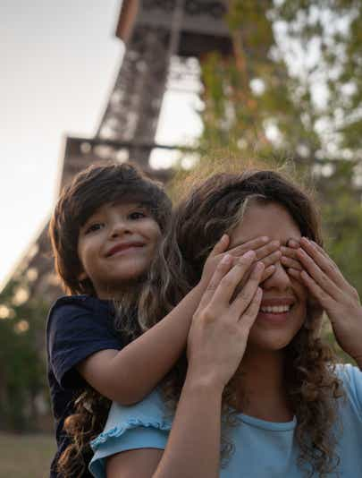 Child cover his mother's eyes in front of the Eiffel Tower in Paris, France