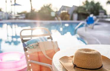 Jennifer's hat sits on a table with swimwear next to the poolside of a Holiday Inn Club Vacation Resort.