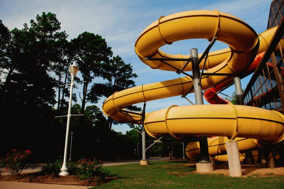 A yellow and orange waterslide protrude from the exterior of an indoor waterpark.
