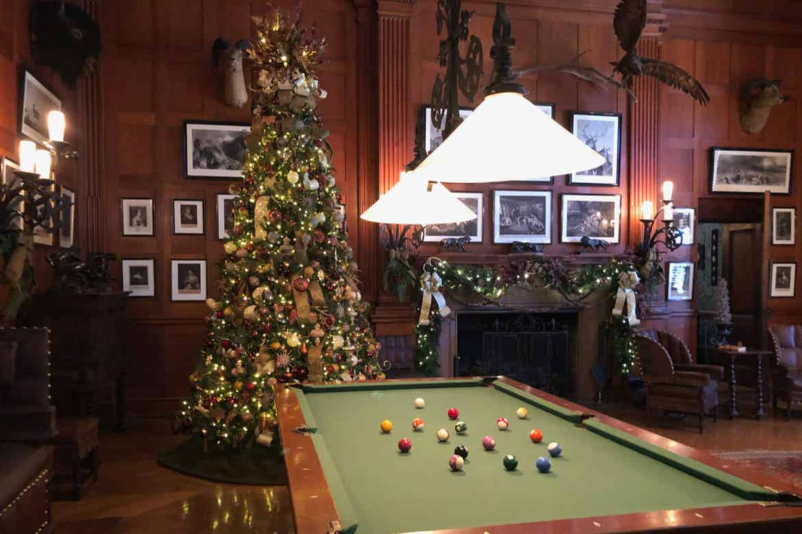 The Recreation Room of the Biltmore Estate with an elaborate fireplace and surrounded by red seating and Christmas trees with a pool table.