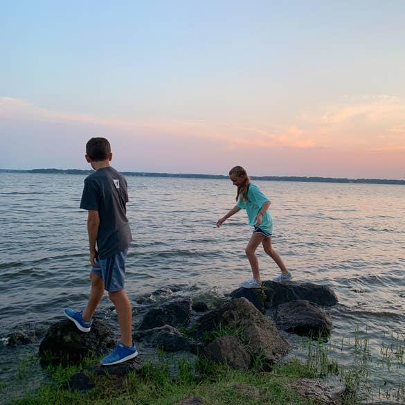 A caucasian boy (left) and girl) climb rocks near the Lake Palestine lakefront.