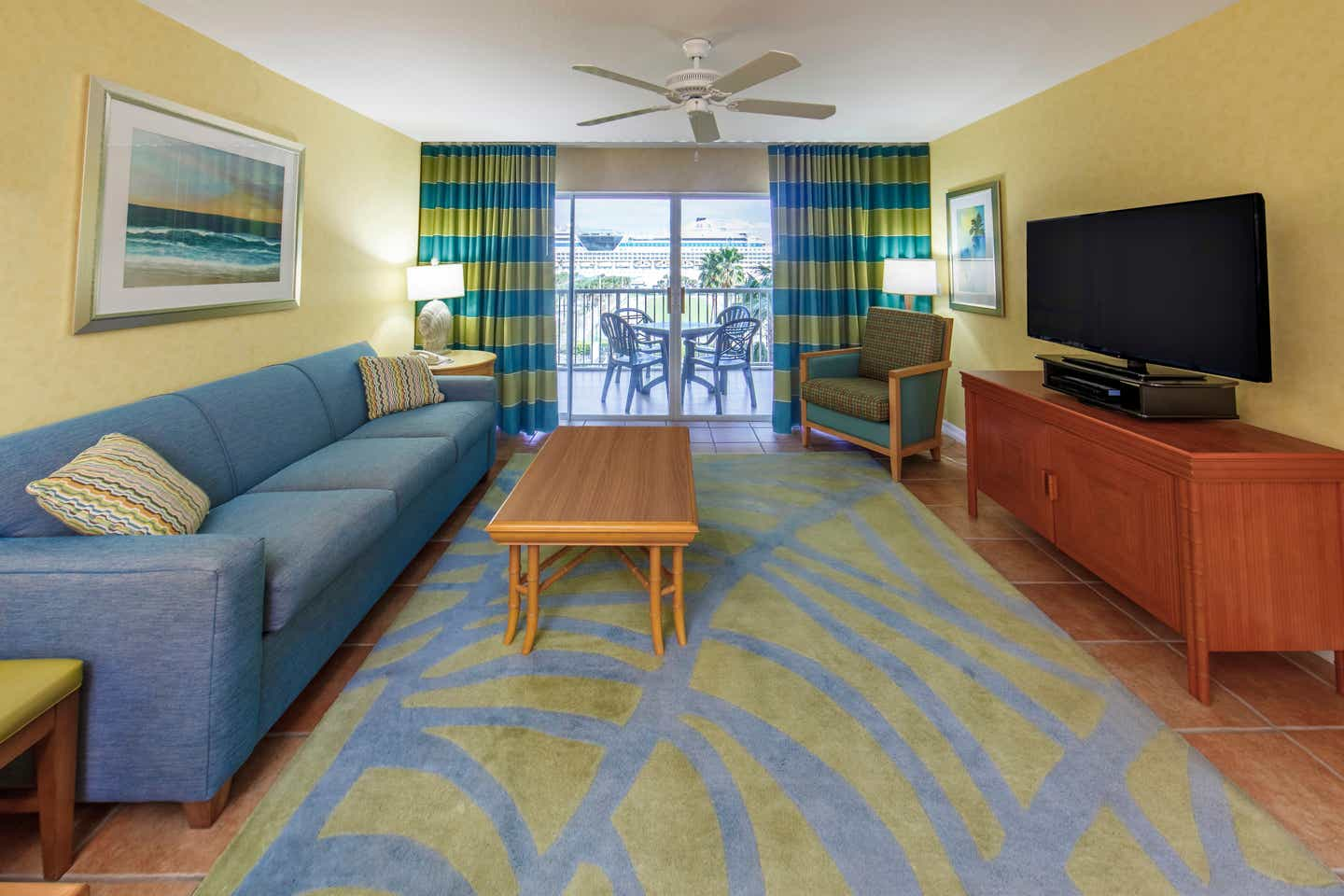 Living room with couch, flat screen TV, and access to a furnished balcony in a two-bedroom lock-off villa at Cape Canaveral Beach Resort