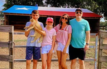 A caucasian family of four stand near a horse stable.