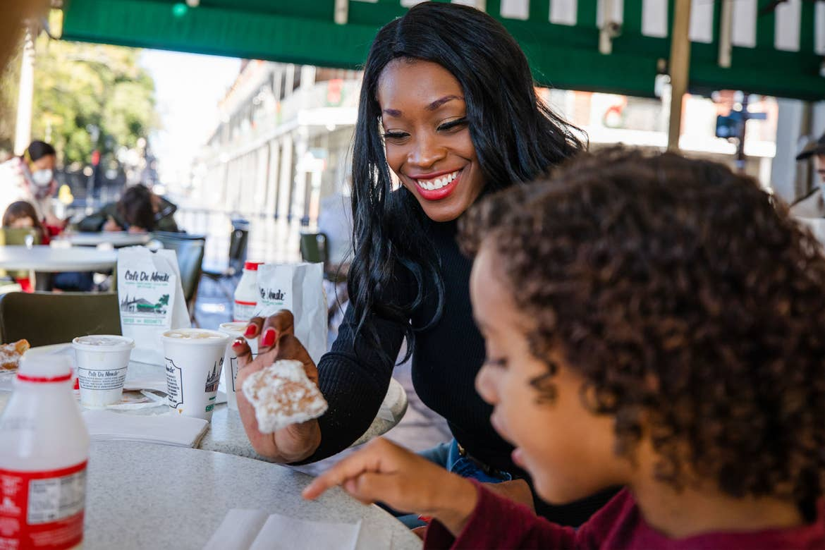Featured contributor, Sally Butan (left) wears a black shirt holding a beignet while her son (right) wears a maroon shirt under a green canopy at Cafe Du Monde eating a powdery beignet.