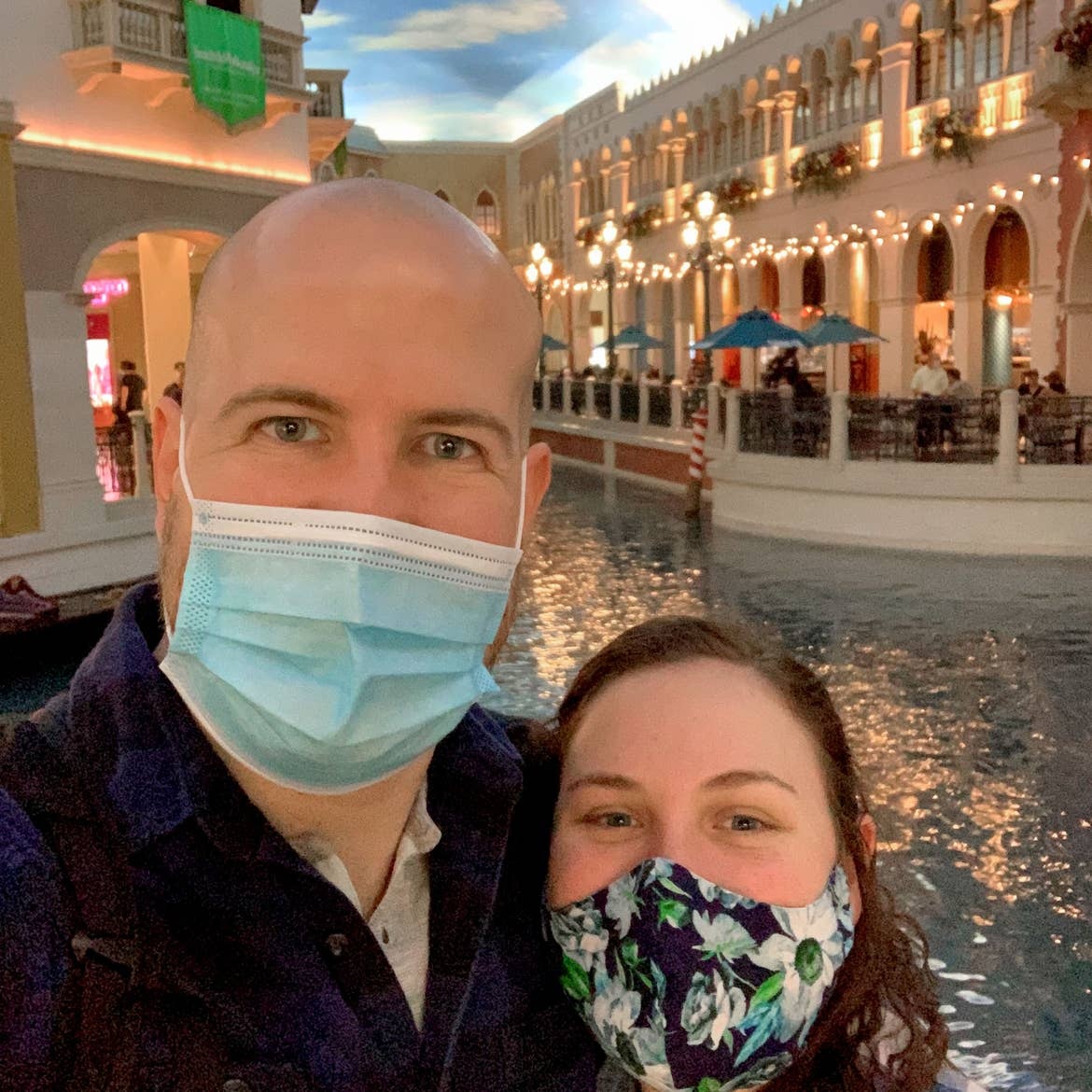 Featured Contributor, Ashley Fraboni (right) and her fiancé, Nicholas (left), wear face masks while posing in front of the canal at the Venetian Las Vegas.